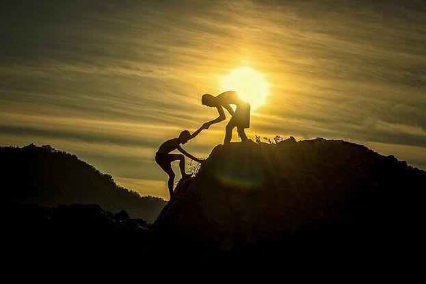 גבר אחד מושיט יד ועוזר לגבר שני לטפס על הר בשקיעה