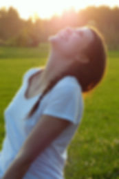 Woman wearing white shirt looking up to the lightof the sun smiling happy