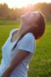 אישה בחצר מוארת מפנה את פניה לאור מלאה בהנאה, חופש וביטחוןבטוחה