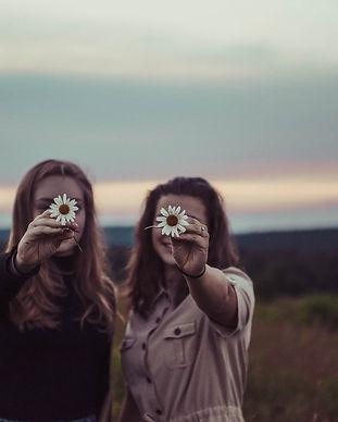 שתי נשים במפגש פרטני אוחזות בפרחים שמסתירם את הפנים שלהן