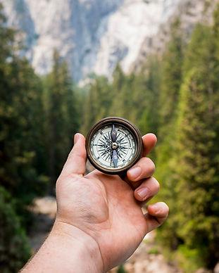 מצפן ביד של אדם בין עצים והרים מראה את הכיוון לתנועה בטוחה בחיים
