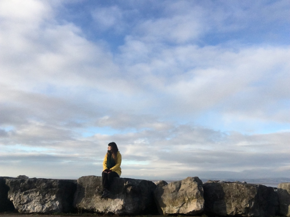 Woman sitting on a rock looking off to the right