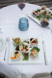 Aperitif-Häppchen auf gedecktem Tisch mit Rotwein und Teelicht