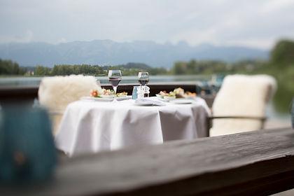 Gedeckter Tisch auf dem Bootsteg vom Bootshaus mit Sicht auf den hoteleigenen Gerzensee und die Berner Alpenkette