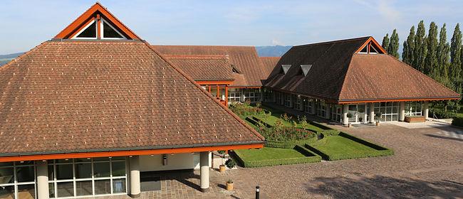 Hotelkomplex vom Hotel Schloss Gerzensee mit Rosengarten und einem Teil der Restaurantterrasse