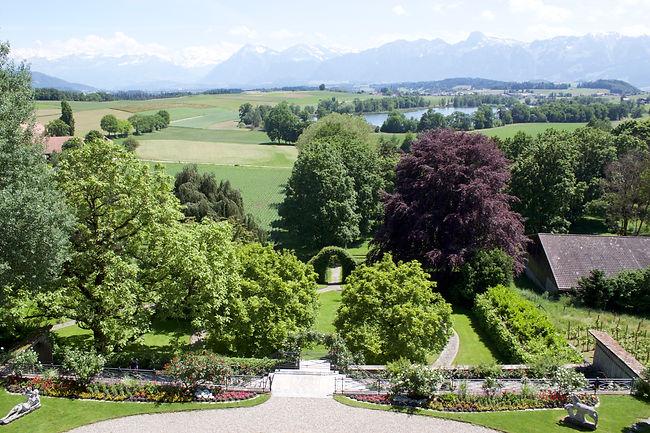 Aussicht vom neuen Schloss Gerzensee über Schlossterrasse und Schlosspark mit Allee und Berner Alpenkette