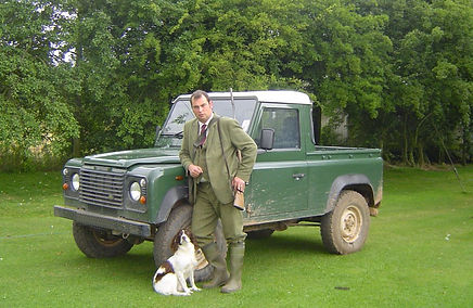 A gamekeeper stands with his dog and Land Rover - ready for work