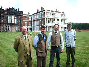 Gamekeepers in front of a stately home