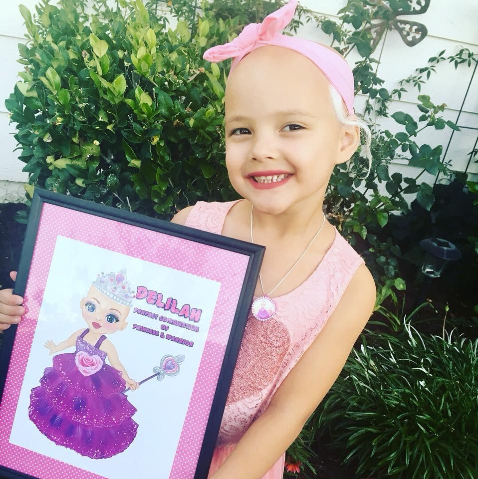 Picture of Delilah holding a poster of Princess Ella