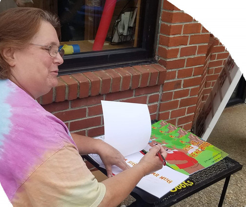 Signing a book at street fair 7-19.jpg