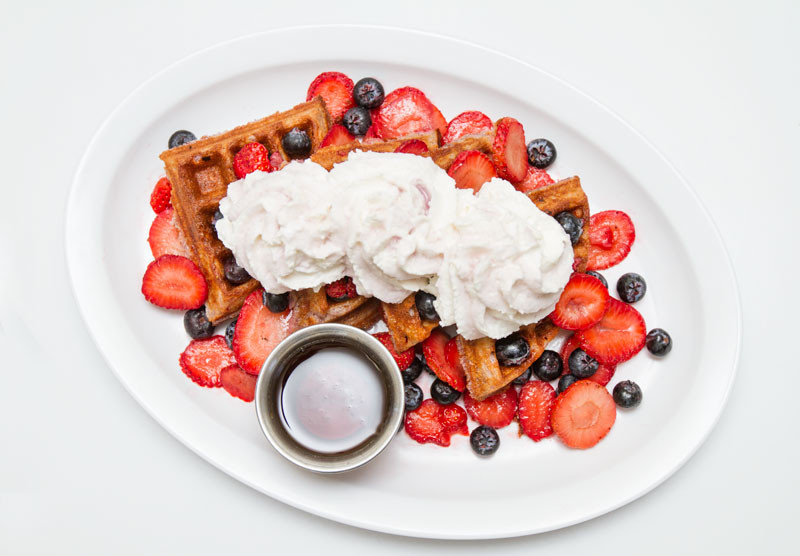 Waffles covered in berries and whipped cream, with syrup on the side.