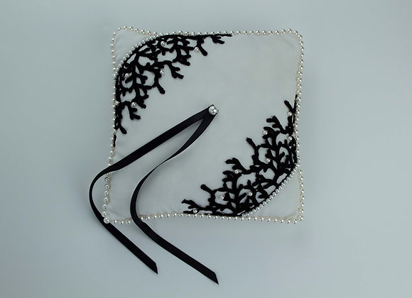 White silk wedding ring pillow decorated with black coral shaped lace and white pearls all around the edge