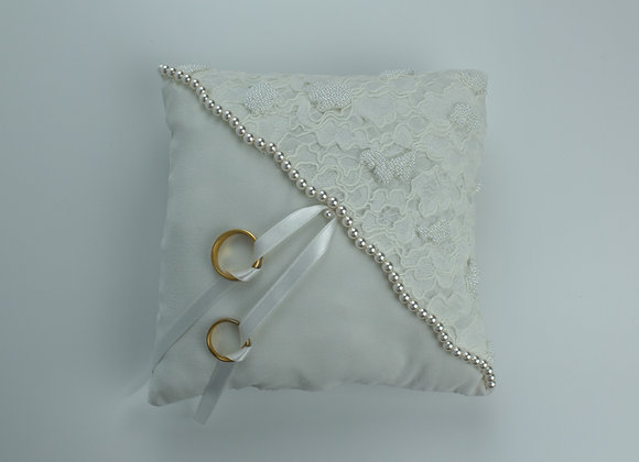 Half white silk and half white lace wedding ring pillow with pearls across the middle and two gold rings attached with ribbon