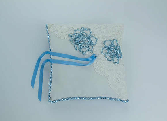 White wedding ring pillow half decorated with lace and blue seed bead embroidery and the other half with blue pearls.