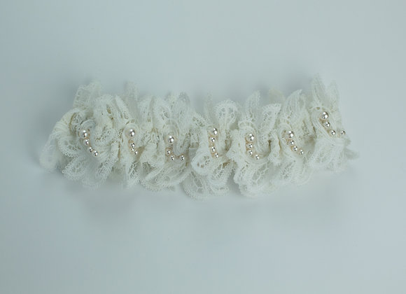 Highly ornate white macramé lace bridal garter decorated with small white pearls throughout