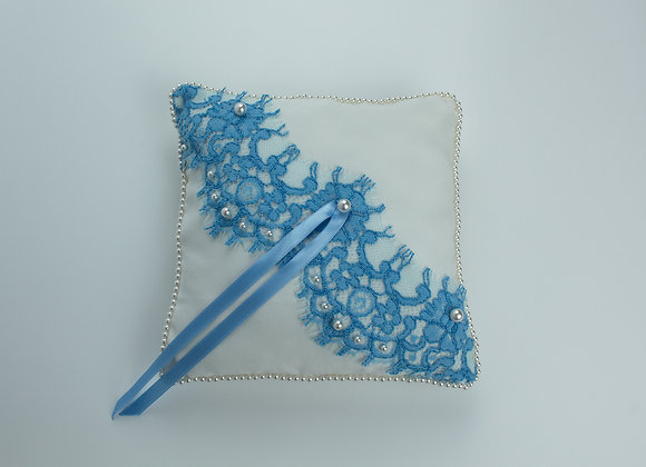 White silk wedding ring pillow decorated with a blue lace and white pearls on top and more pearls all around the edge