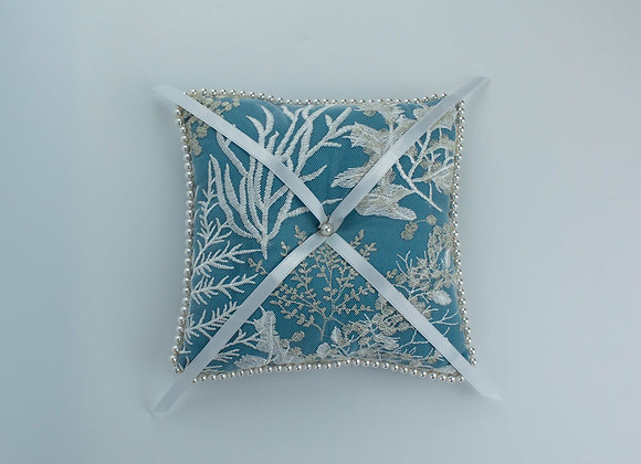 Teal wedding ring pillow with an overlay of sea themed white and silver lace on top and edges decorated with white pearls.