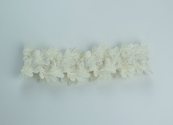 Top view of a white vintage lace bridal garter decorated with small white pearls