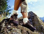 Foto das pernas de uma pessoa caminhando as pedras