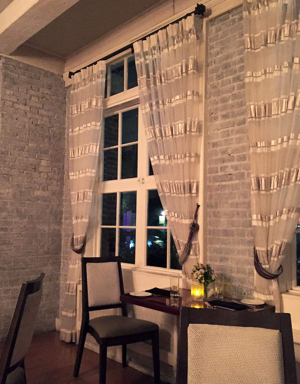 the restaurant's painted gray brick walls with soft gray curtains