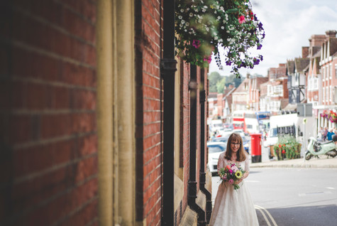 Bride walks down the side of a red brick building towards photographer holding her bouquet