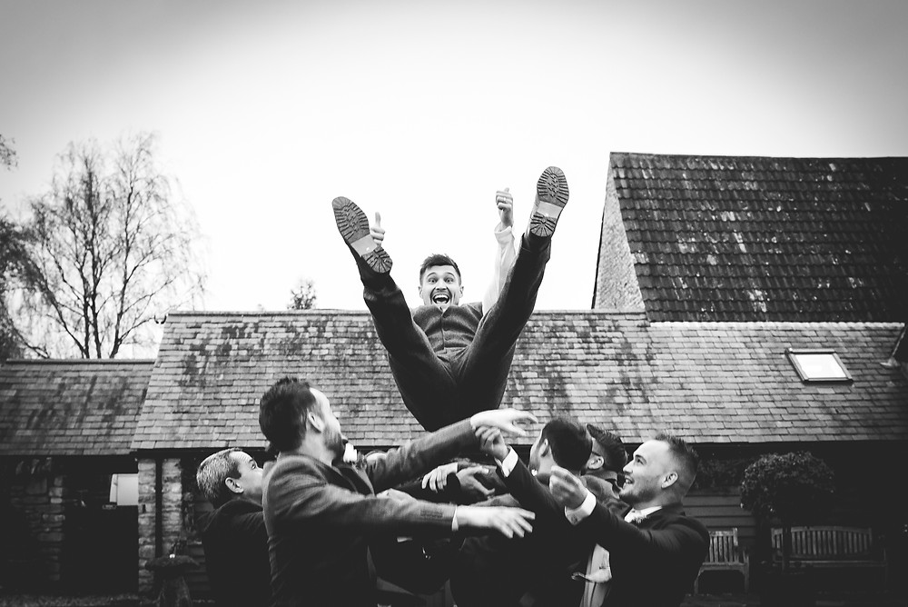 Groom in mid air with his thumbs up having been thrown up by his friends