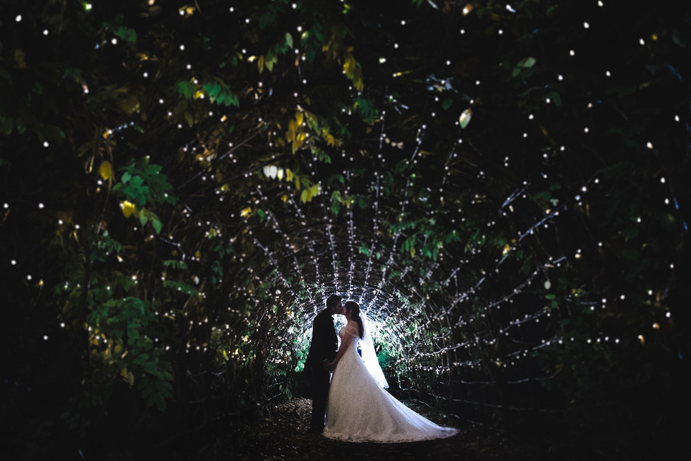 bride and groom under a tunnel of fairy lights in the dark at tortworth court gloucestershire