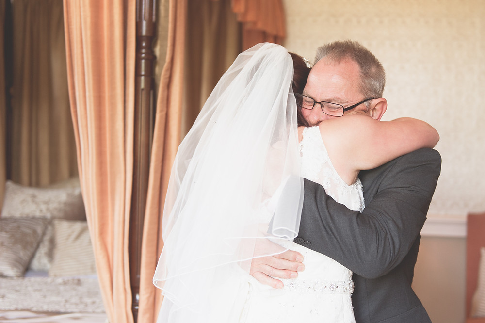 father of the bride hugs his daughter