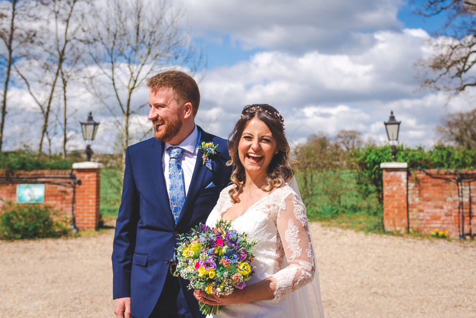 Bride and groom outside. Bride looking and laughing at camera holding flowers