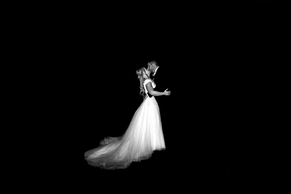 spotlight black and white of bride and groom kissing on steps in the dark. bride wears full skirted dress with a train