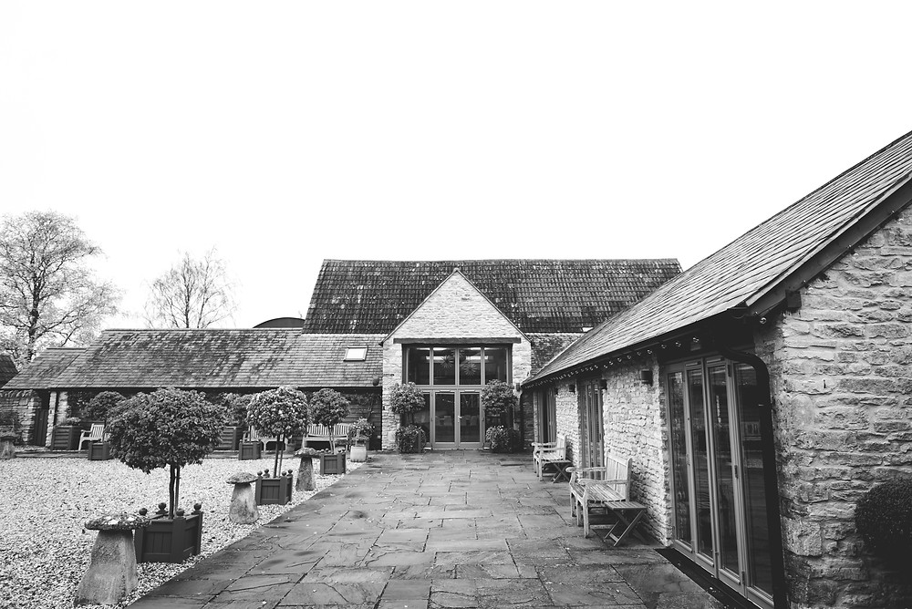 Black and white photo of Winkworth Farm from the courtyard, lined with bay trees