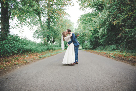 bride and groom kissing on a wiltshire country lane. bride has hands loosely wrapped around grooms neck and is leaning back