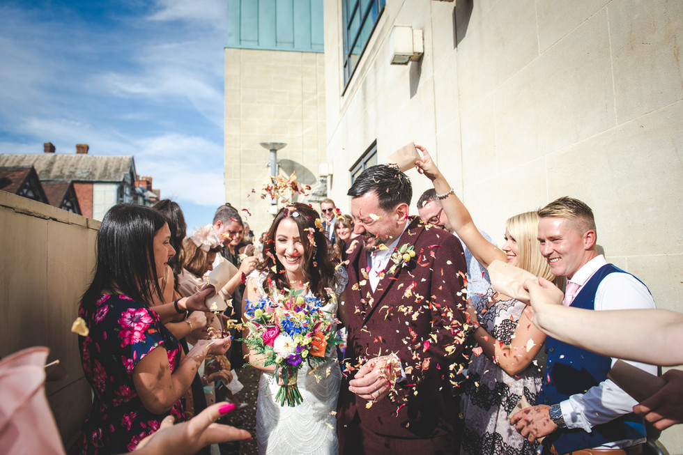Bride and groom walking through guests throwing confetti at the left bank in hereford