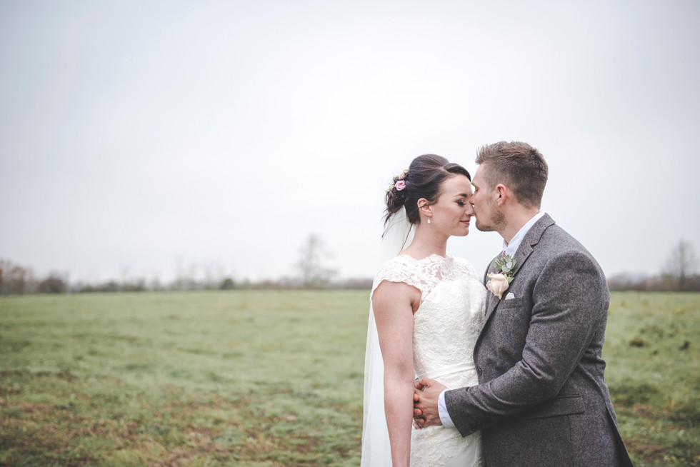 bride and groom in a field in winter. groom is kissing bride gently on the end of her bose