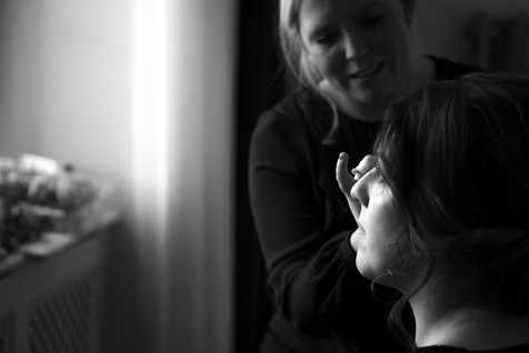 black and white photo of bride bridesmaid having her make up done by Lisa Ellis at Tortworth Court Gloucestershire