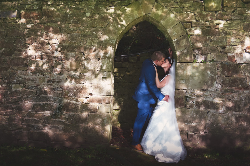 bride and groom in wall archway