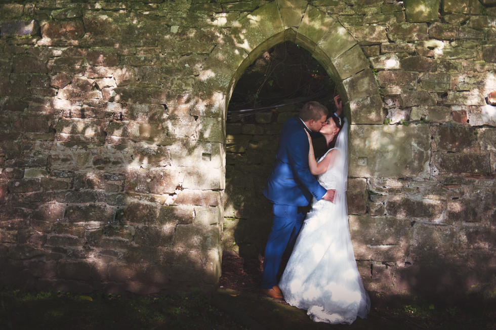 bride and groom in stone archway against wall at clearwell castle gloucestershire in dappled sunlight
