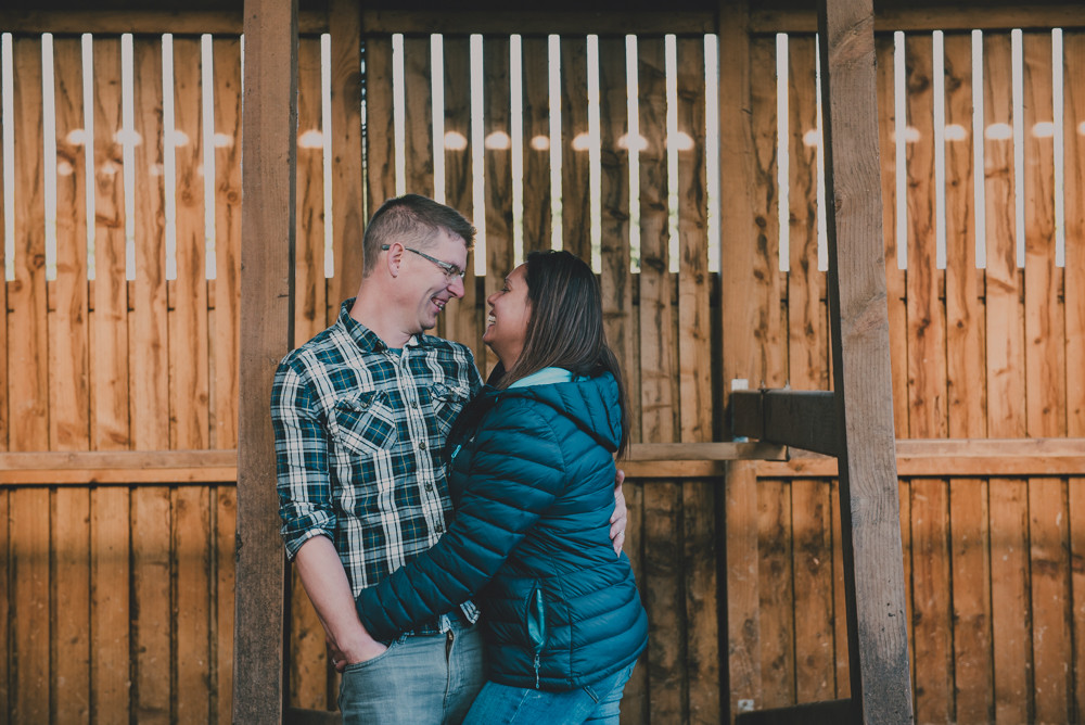 Couple laughing in cow shed
