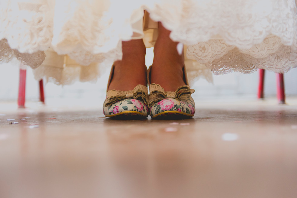 brides feet in irregular choice shoes under dress with confetti lying on the floor around feet
