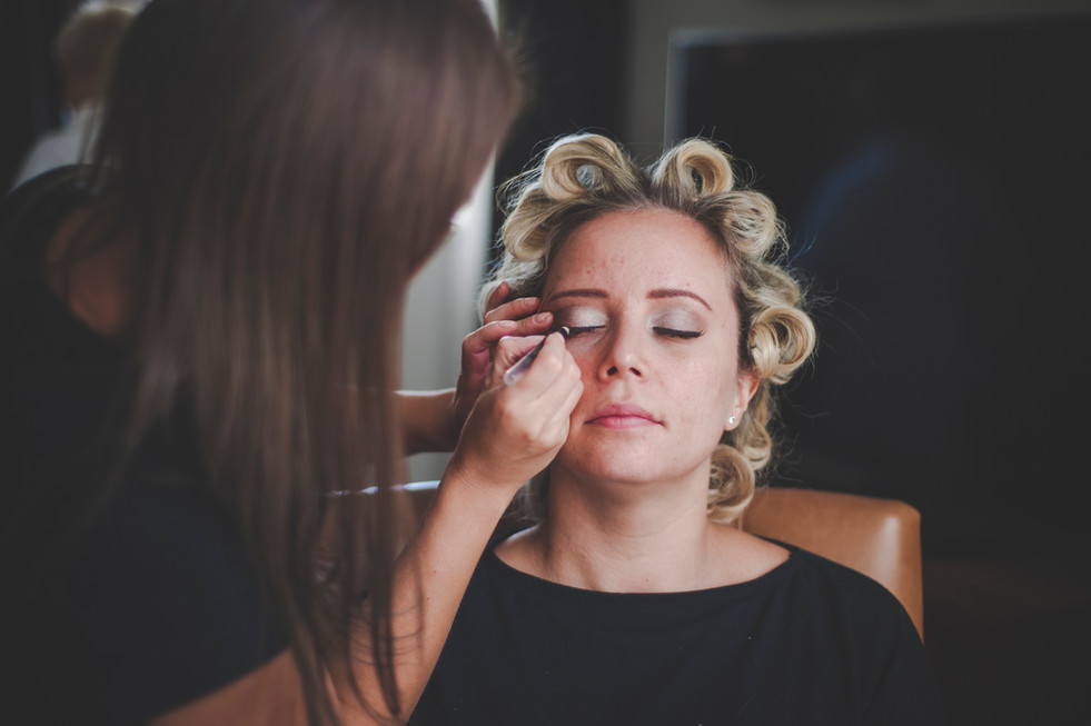 Bride having her makeup applied with her hair setting in rollers at Tortworth Court Gloucestershire