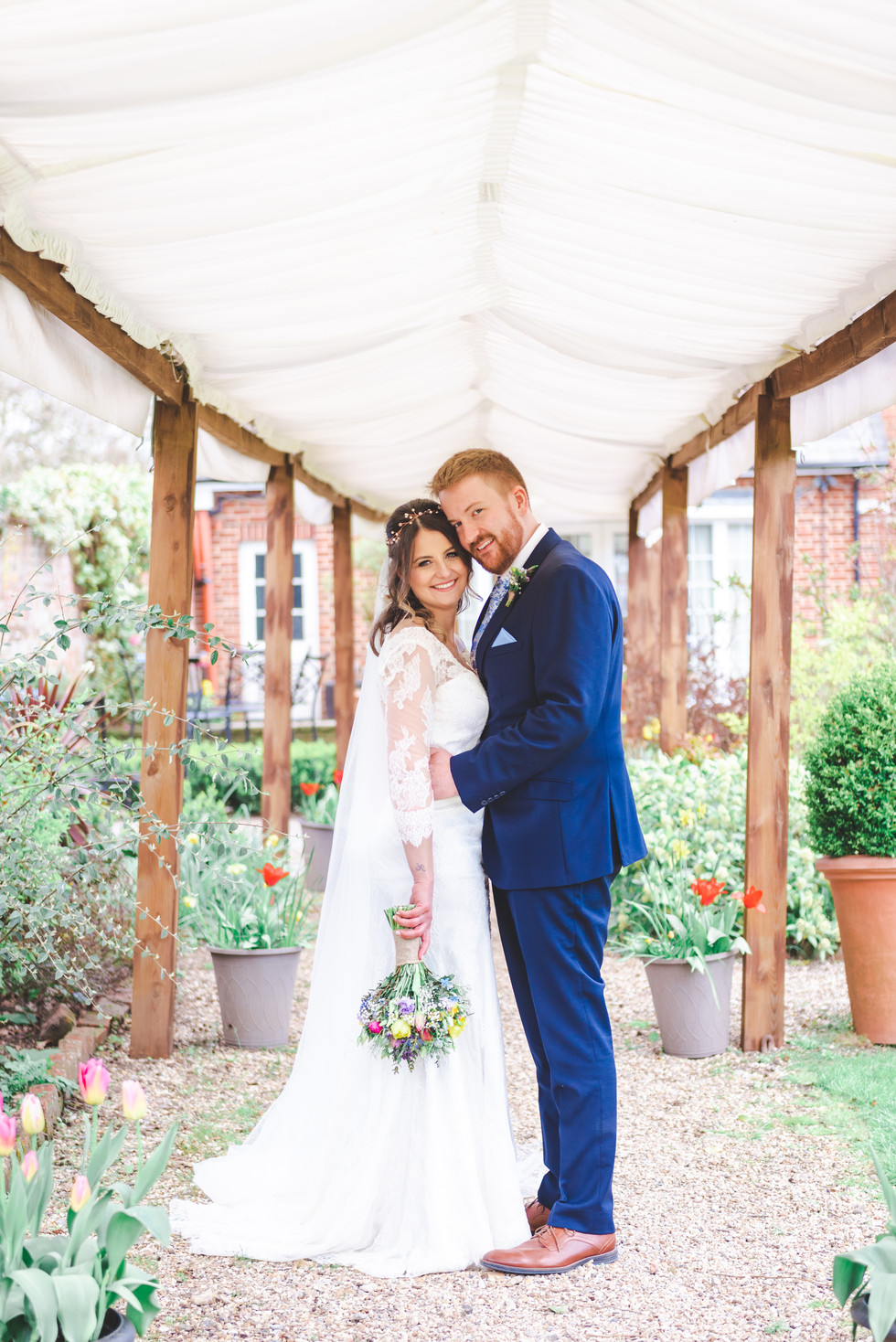 Bride and Groom stand under marquee archway surrounded by plants and flowers