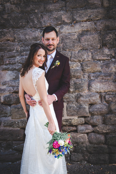 Bride and groom standing against wall in Hereford