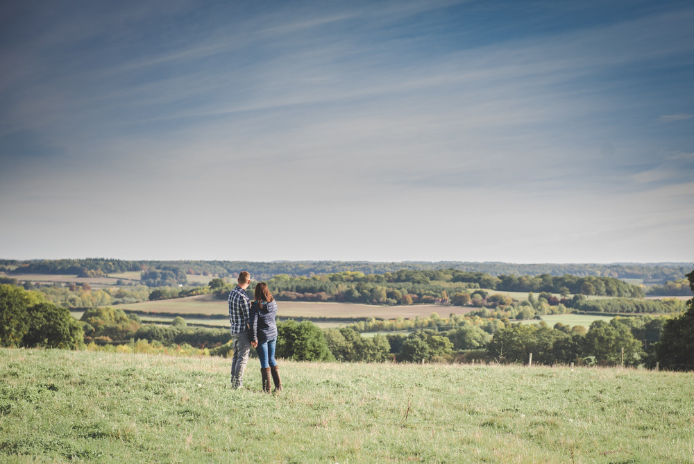 Couple look at view over Berkshire Wiltshire and Gloucestershire