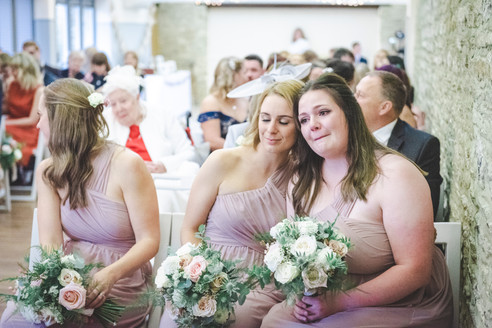three bridesmaids sat in ceremony at winkworth farm wiltshire. one bridesmaid crying, another leaning against her to comfort her.