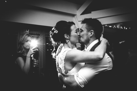 Black and white photograph of bride and grooms first dance. guest in background using her phone and flash backlights bride and groom