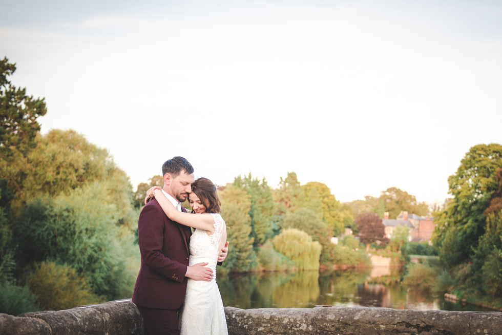 Bride and Groom stood on Bridge overlooking the River Wye in Hereford at Left Bank Village