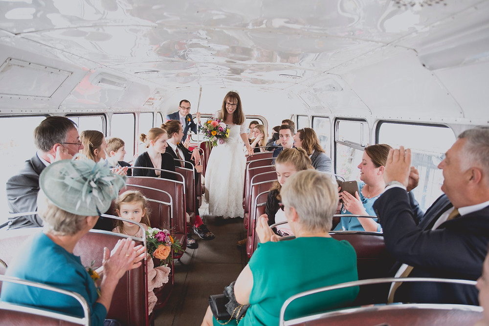 Bride and groom get on bus
