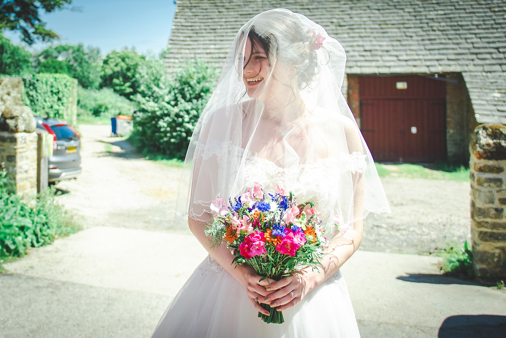 Beautiful bride stands in the sunlight with her veil down holding her colourful bouquet of flowers