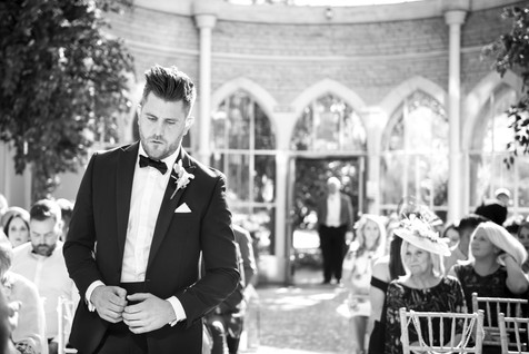 Groom stood nervously waiting for his bride at the orangery tortworth court gloucestershire. toastmaster stood in the doorway behind him