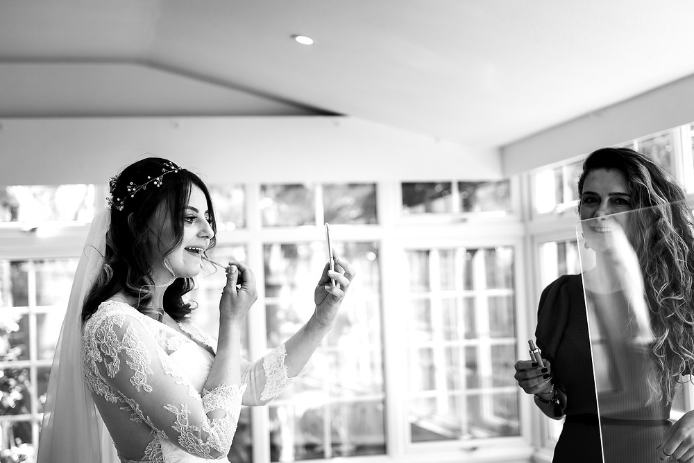 Bride touching up lipstick before ceremony